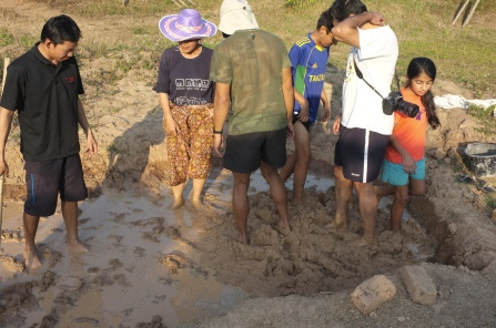 First step, pour some binder like rice husk or straw onto the mud and mix it in with your feet.