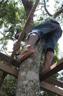 Salim hammering the roof frame at an awkward angle.