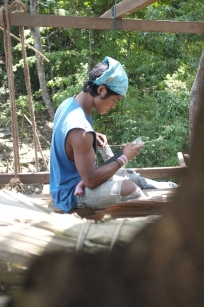 Wira uses his parang (machete) to make strings from vines.