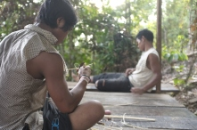 Salim taking a break and Wira playing with his knife.